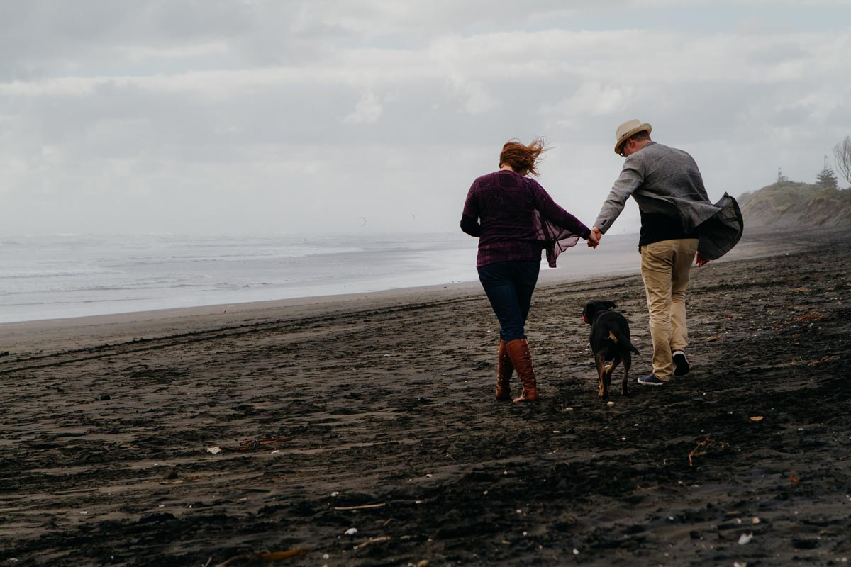 Pet portrait photo of dog and owners walking on muriwai beach in auckland by sarah weber photography