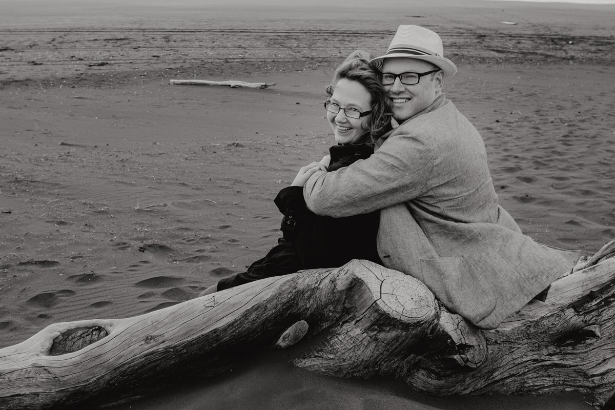 Couple portrait photo cuddling at muriwai beach in auckland by sarah weber photography