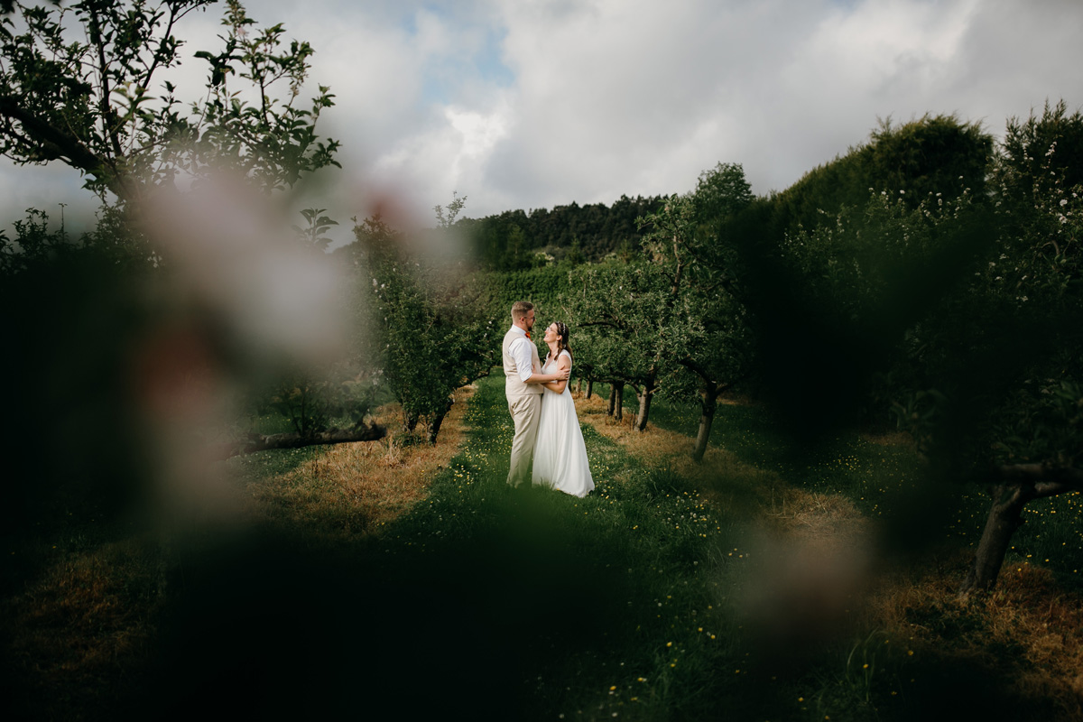 Auckland bride and groom huging in Windmill Orchards from coatesville settlers hall wedding