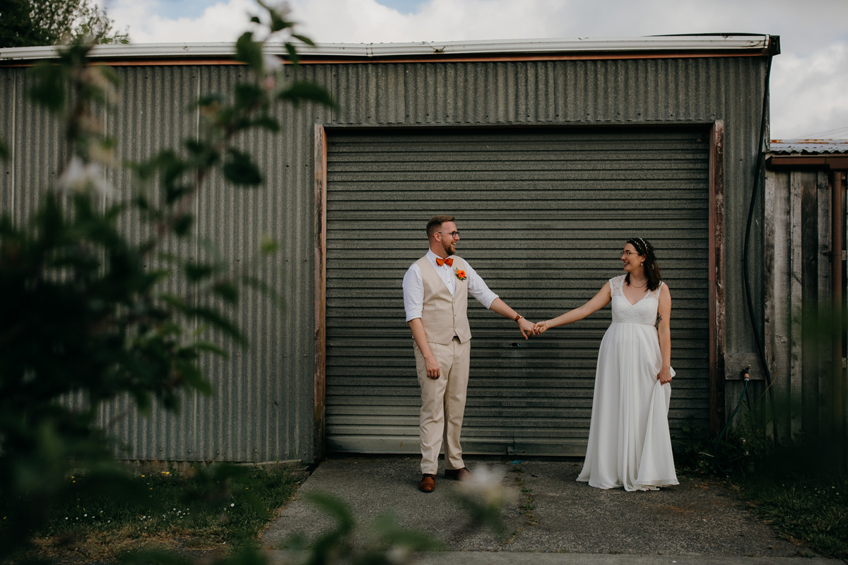coatesville settlers hall wedding auckland bride and groom stnading outside shed Windmill Orchards
