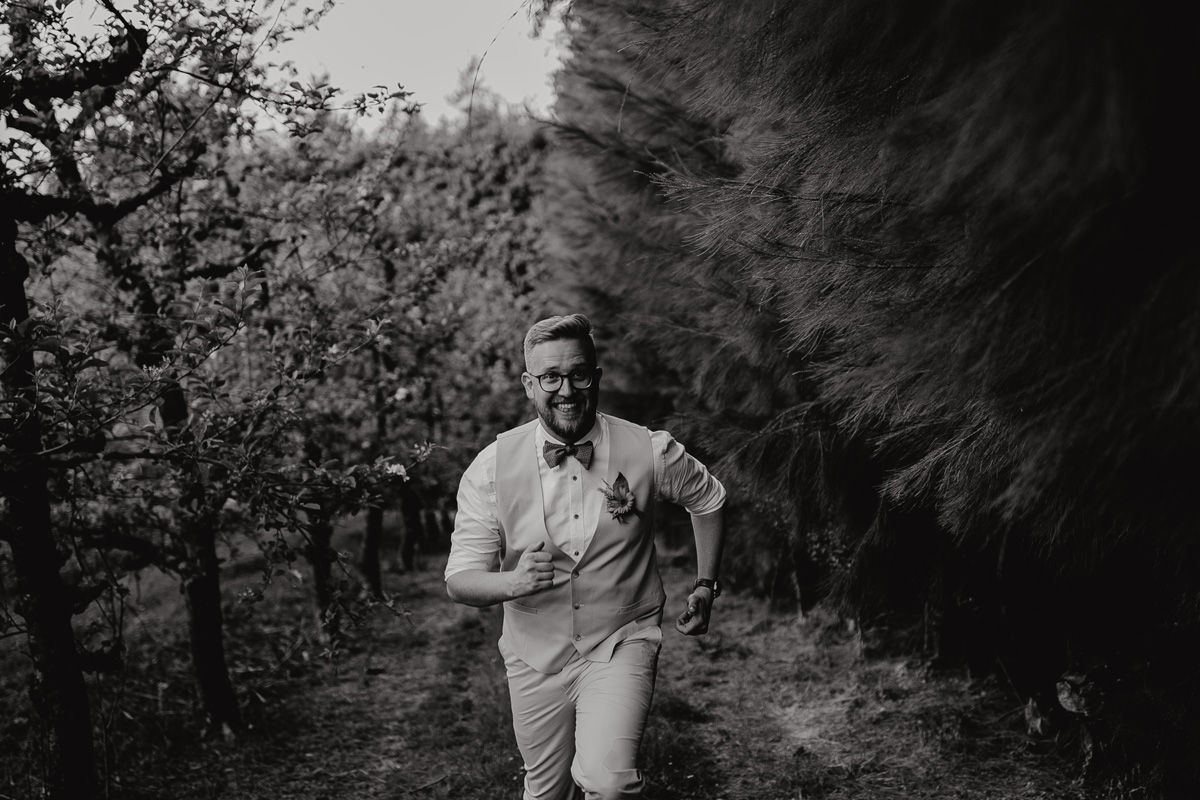 coatesville settlers hall wedding auckland groom running in Windmill Orchards by sarah weber photography