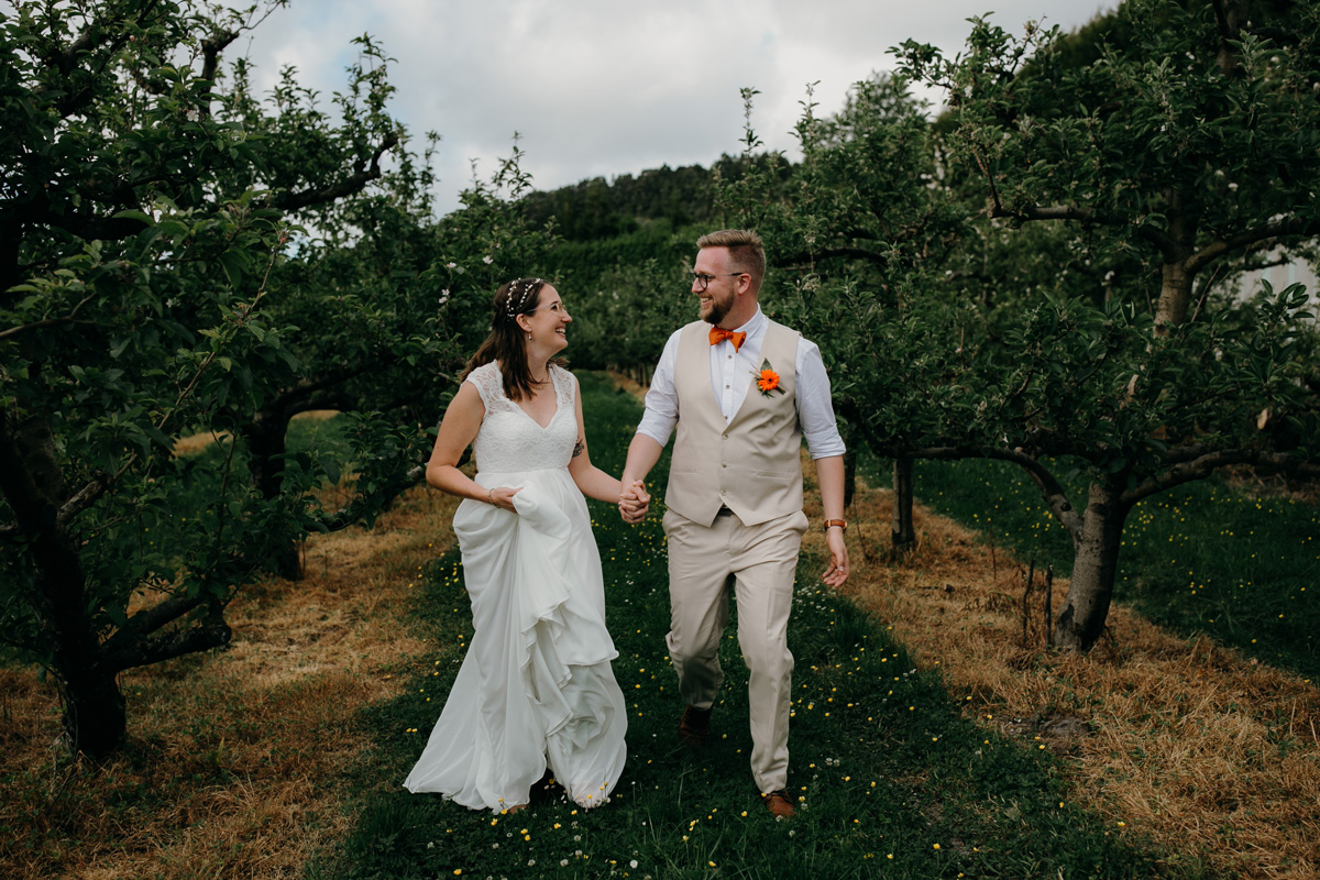 coatesville settlers hall wedding auckland bride and groom running in Windmill Orchards by sarah weber photography