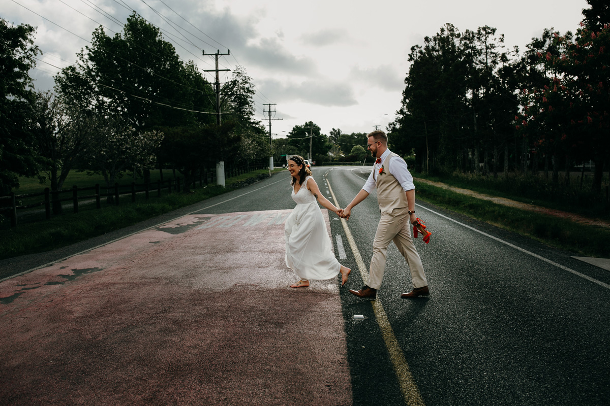 coatesville settlers hall wedding auckland bride and groom running on road photos by sarah weber photography