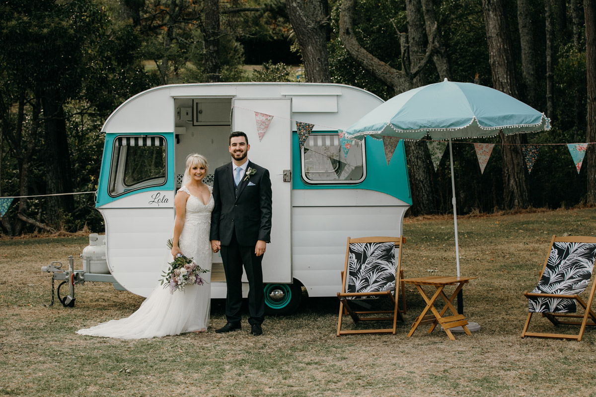 Bride and Groom posing infront of Caravan at The Brigham Restaurant & Cafe in Whenuapai, Auckland photo by Sarah Weber Photography