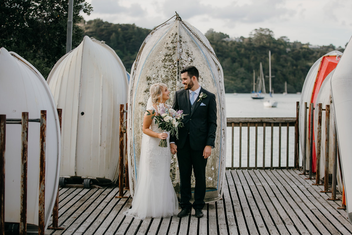 Bride and Groom posing infront of dinghy at Herald Island Wharf in Whenuapai, Auckland photo by Sarah Weber Photography