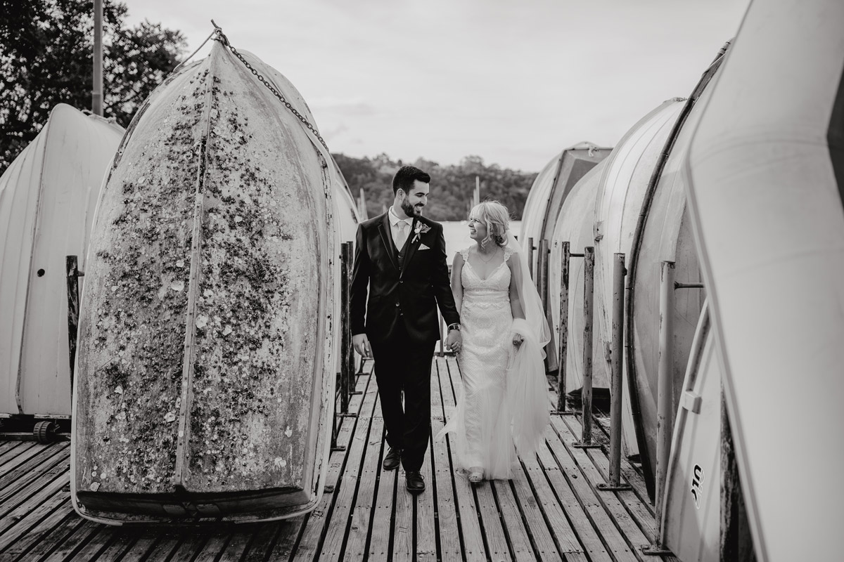 Bride and Groom walking between boats at Herald Island Wharf in Whenuapai, Auckland photo by Sarah Weber Photography