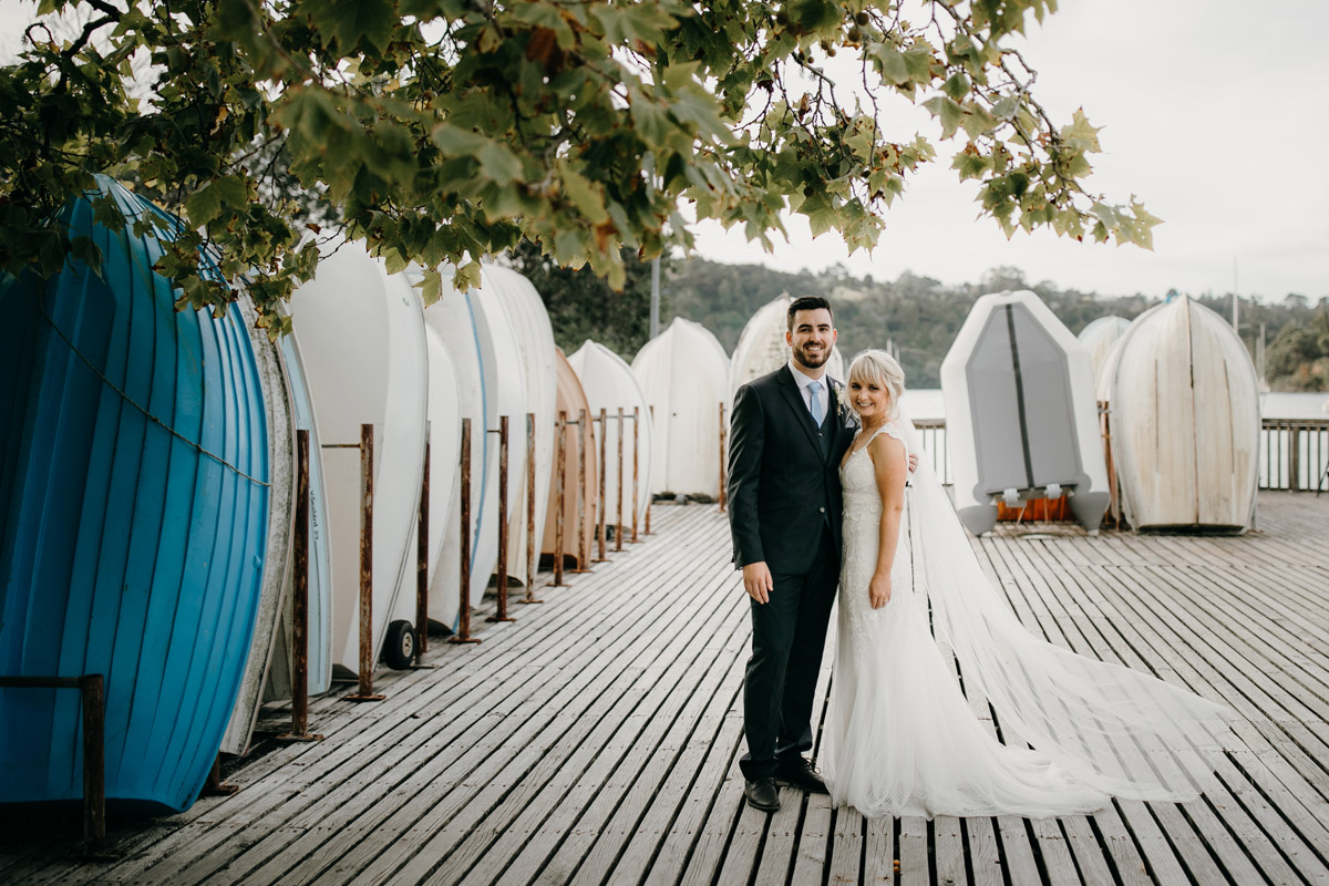 Bride and Groom posing at Herald Island Wharf in Whenuapai, Auckland photo by Sarah Weber Photography