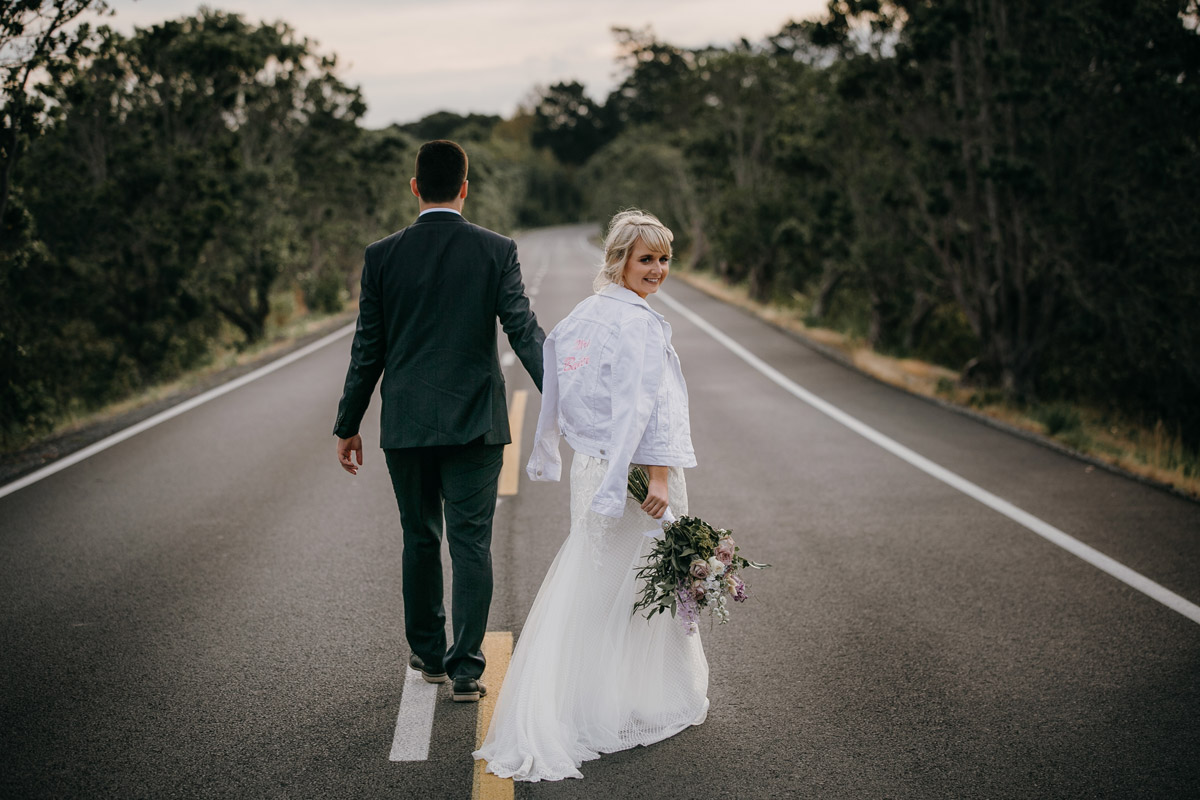 Bride and Groom walking on Herald Island Road in Whenuapai, Auckland photo by Sarah Weber Photography