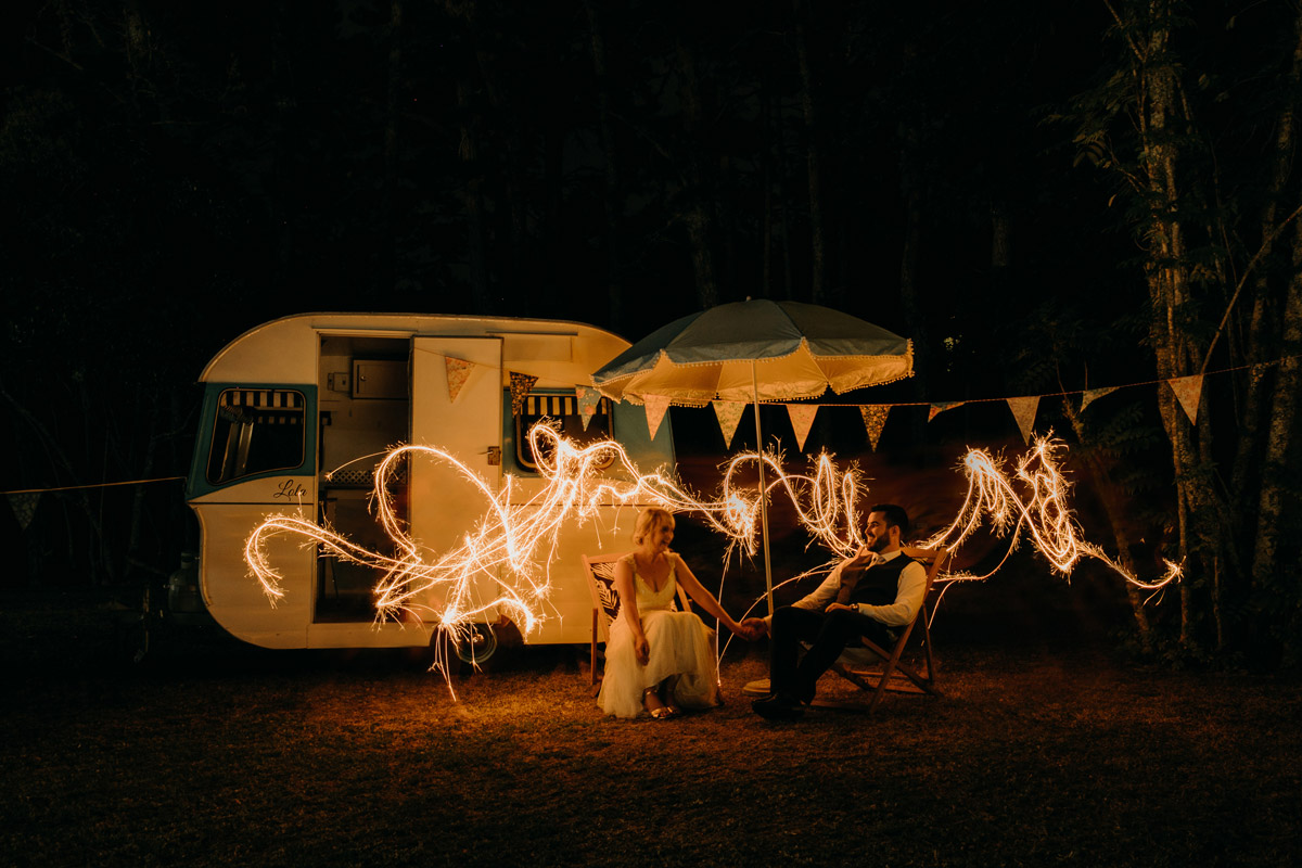 Bride and Groom sit infront of caravan with long exposure sparklers at The Brigham wedding reception photo by Sarah Weber Photography