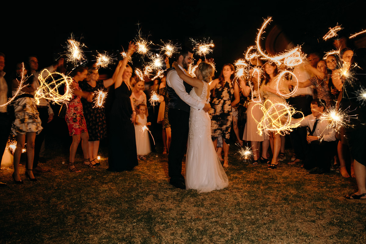 Bride and Groom hug guests holding night sparklers at The Brigham wedding reception photo by Sarah Weber Photography