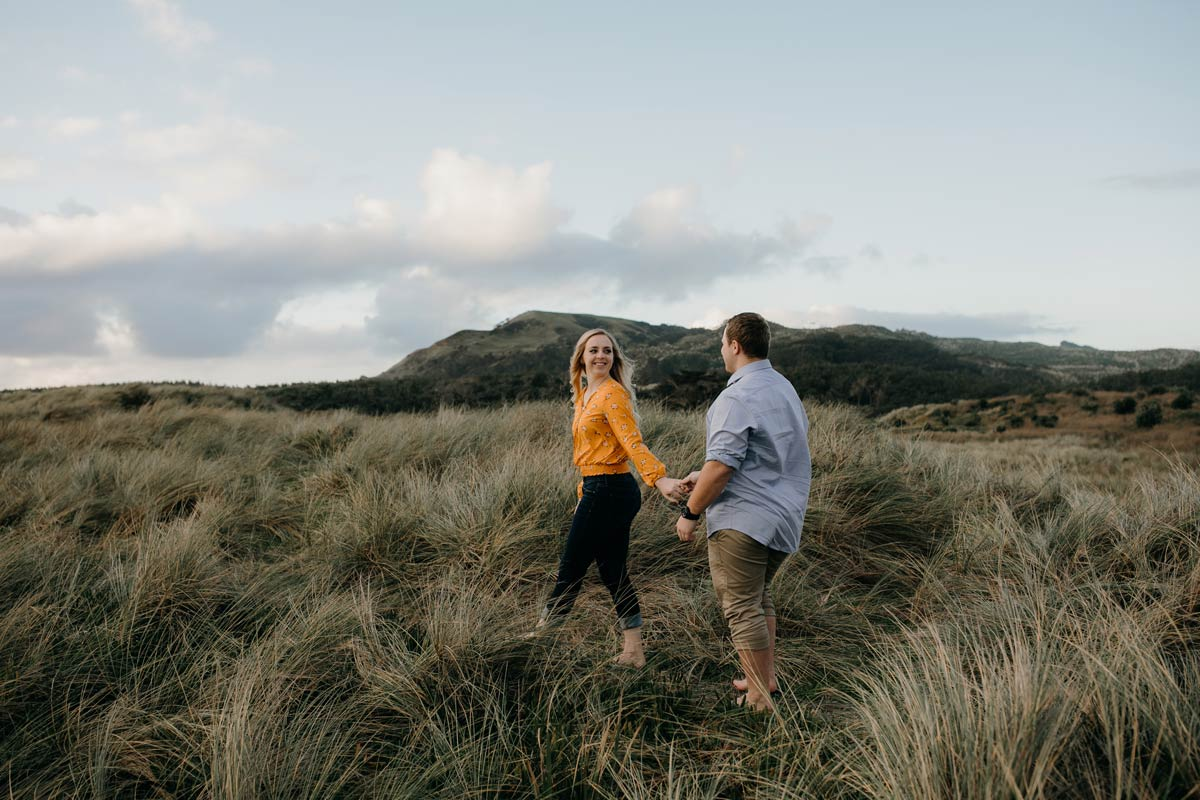 couple walking along muriwai beach auckland new zealand during a golden light evening lifestyle engagment pre-wedding photoshoot session by sarah weber photography