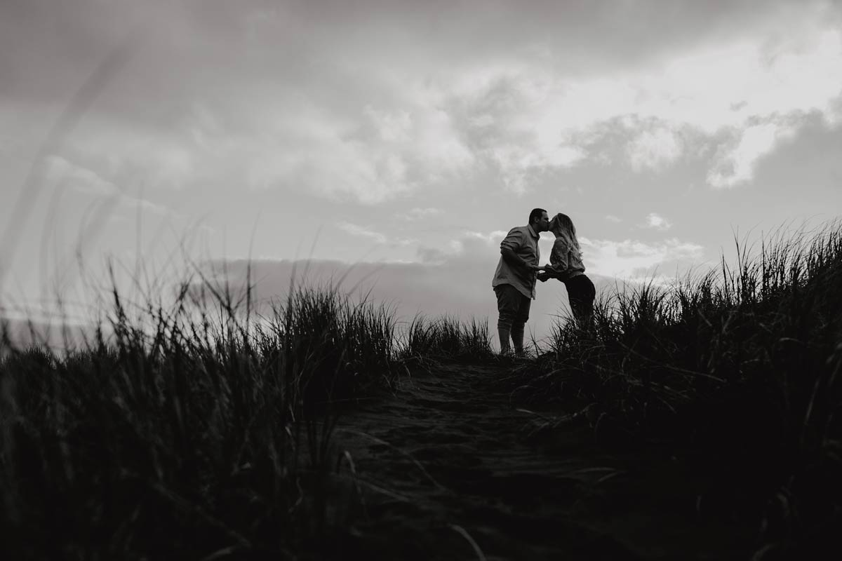 silhouette of couple kissing at muriwai beach auckland new zealand during a golden light evening lifestyle engagment pre-wedding photoshoot session by sarah weber photography