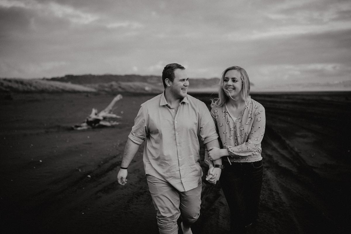 happy couple walking along muriwai beach auckland new zealand during a golden light evening lifestyle engagment pre-wedding photoshoot session with sarah weber photography