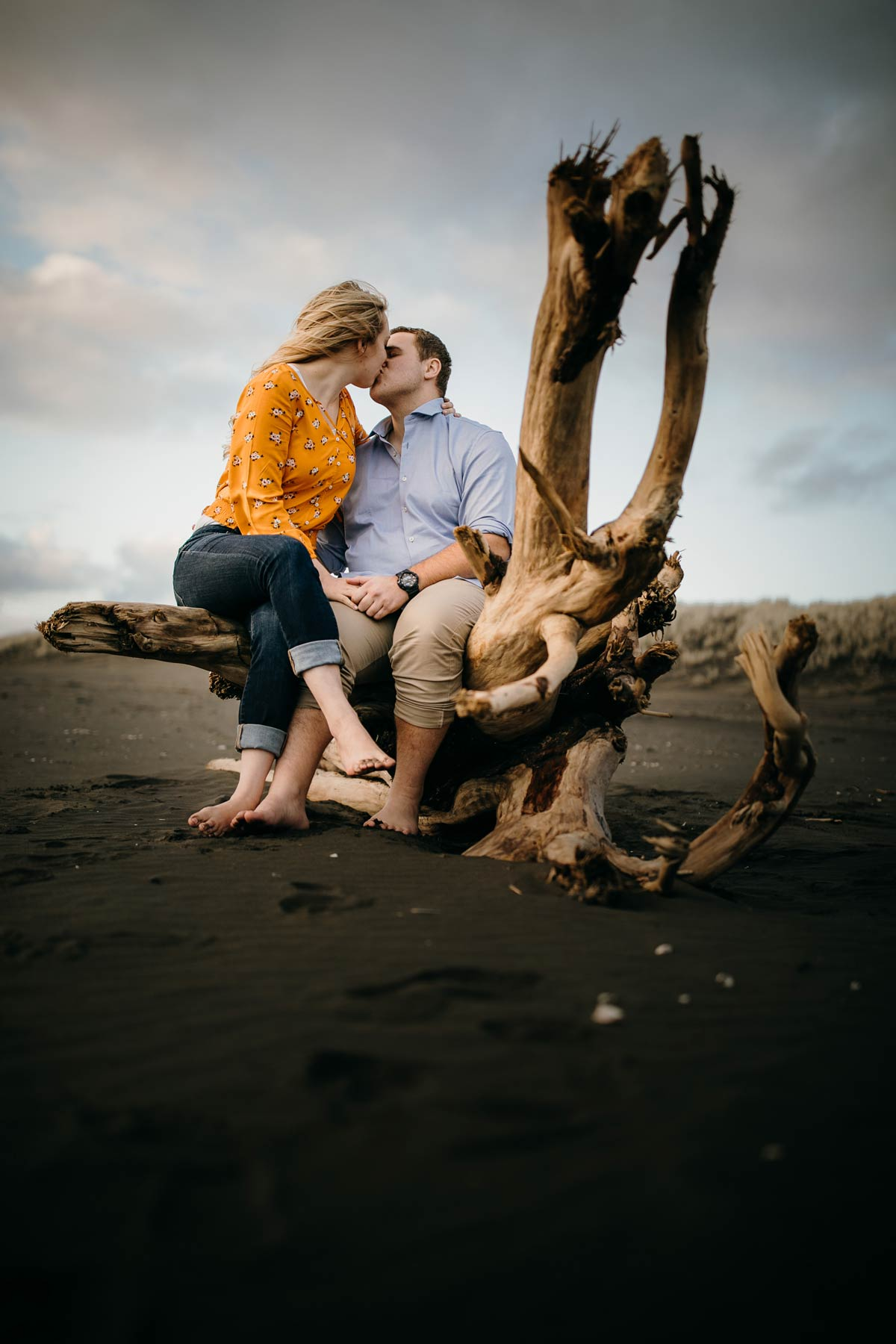 couple sitting and kissing on driftwood log at muriwai beach auckland new zealand during a golden light evening lifestyle engagment pre-wedding photoshoot session by sarah weber photography