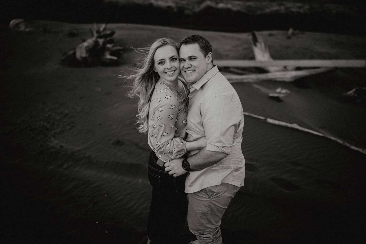 portrait of couple smiling at camera muriwai beach auckland new zealand during a golden light evening lifestyle engagment pre-wedding photoshoot session by sarah weber photography