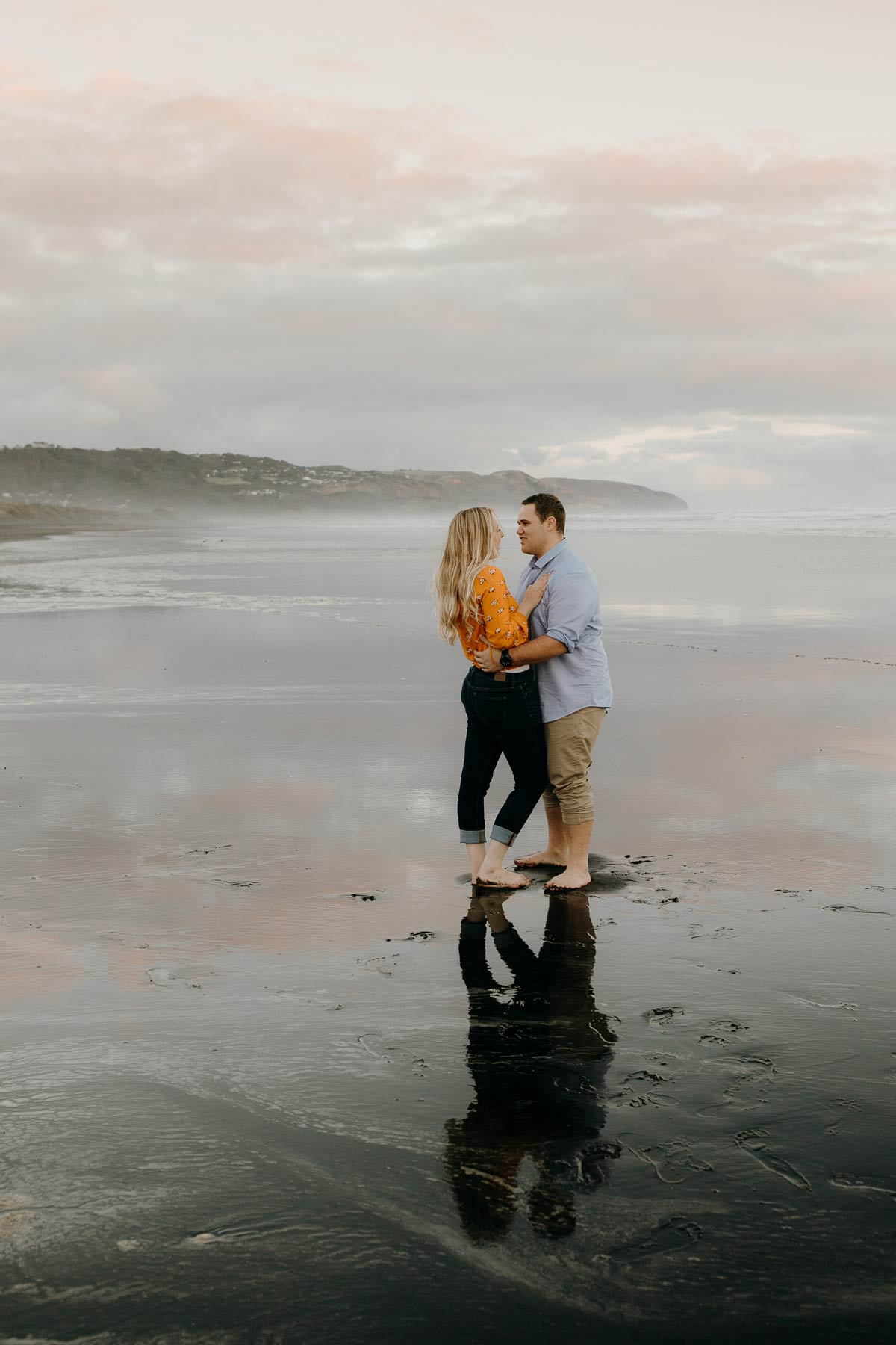 couple embracing with a wet sand reflection during a golden light evening lifestyle engagment pre-wedding photoshoot session at muriwai beach auckland new zealand photos by sarah weber photography