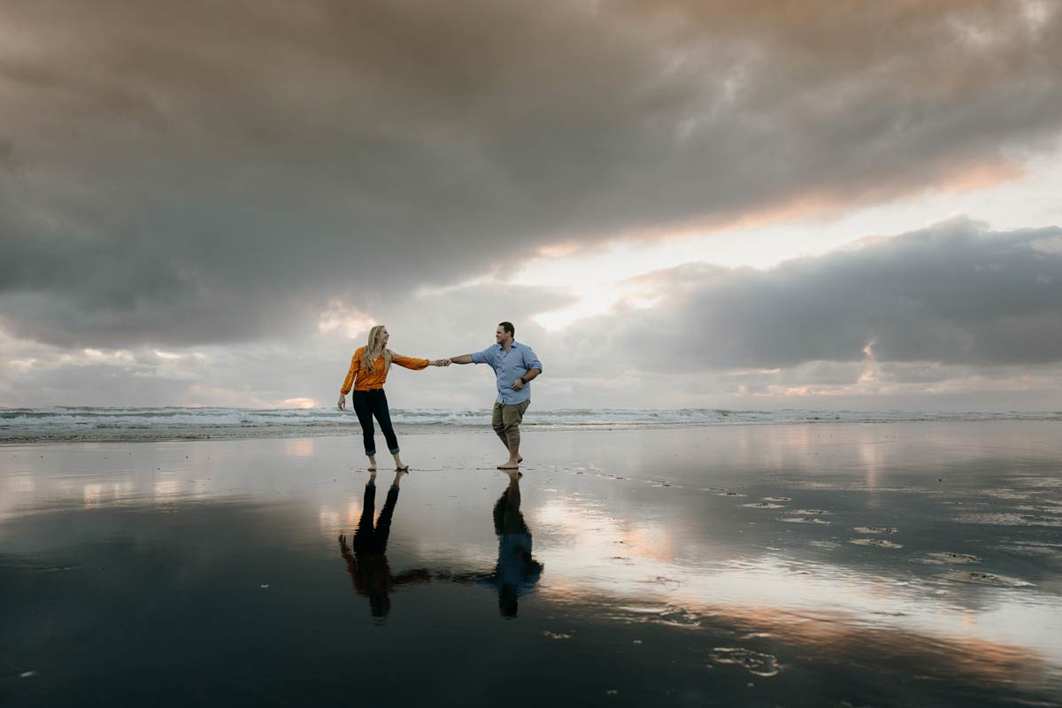couple dancing during a golden light evening lifestyle engagment pre-wedding photoshoot session at muriwai beach auckland new zealand photos by sarah weber photography