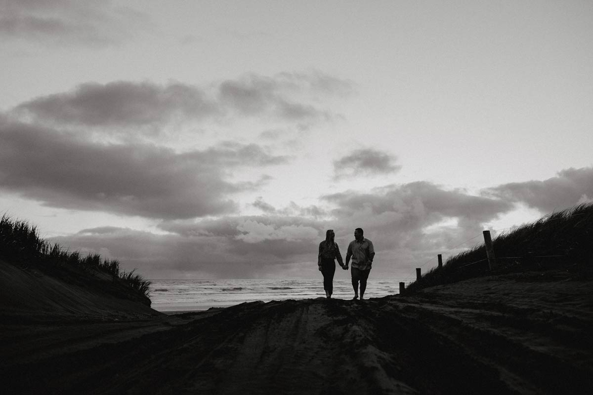 silhouette photo of couple at sunset on muriwai beach auckland new zealand during engagment photoshoot session by sarah weber photography