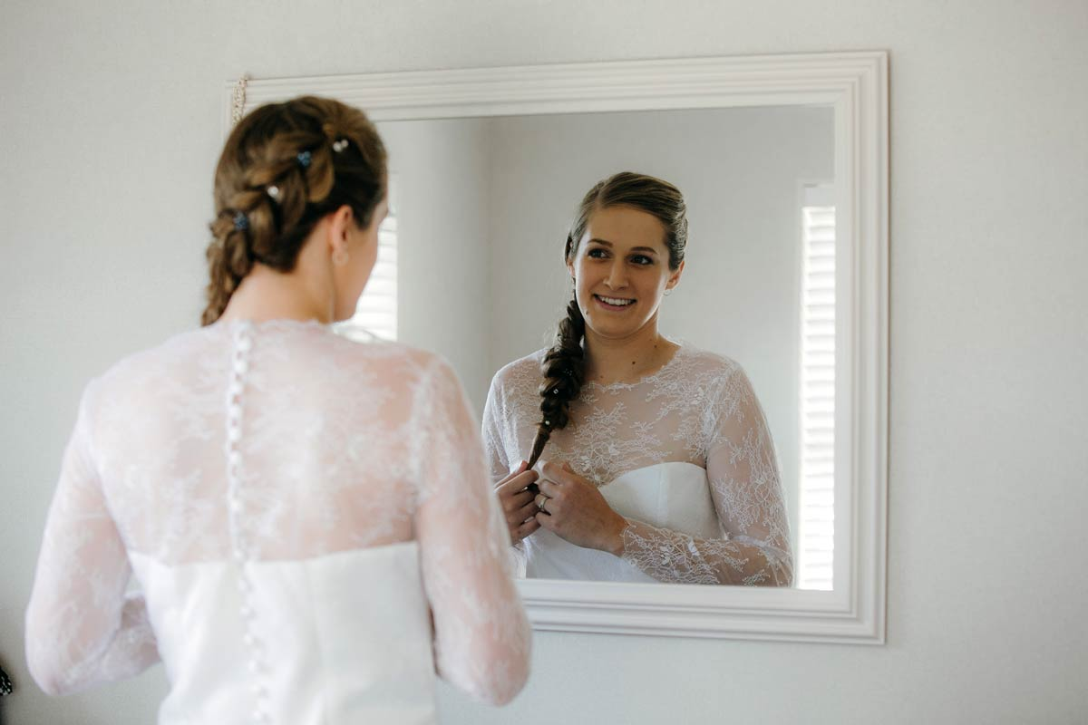 Bride checking hair in mirror ready for bridgewater country estate wedding in Kaukapakapa, Auckland photo by sarah weber photography