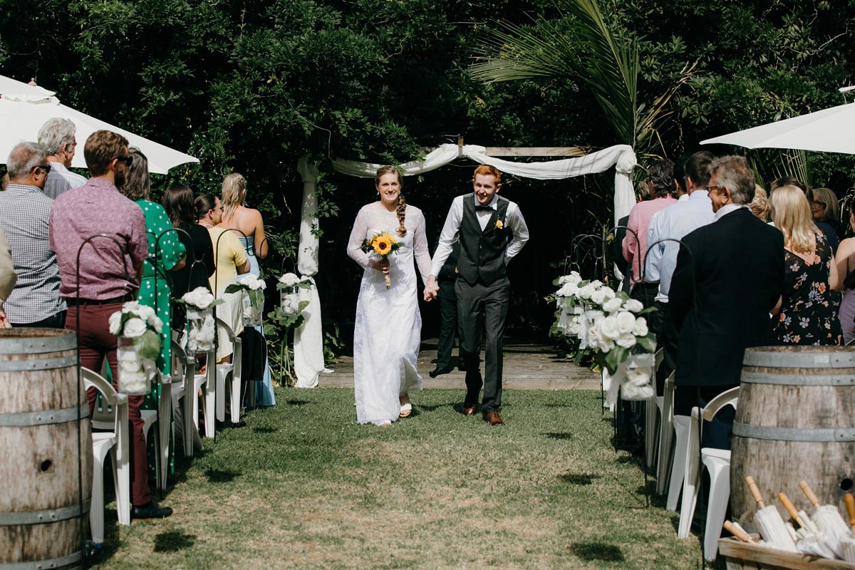 bride and groom walking down aisle at bridgewater country estate venue in Kaukapakapa, Auckland photo by sarah weber photography