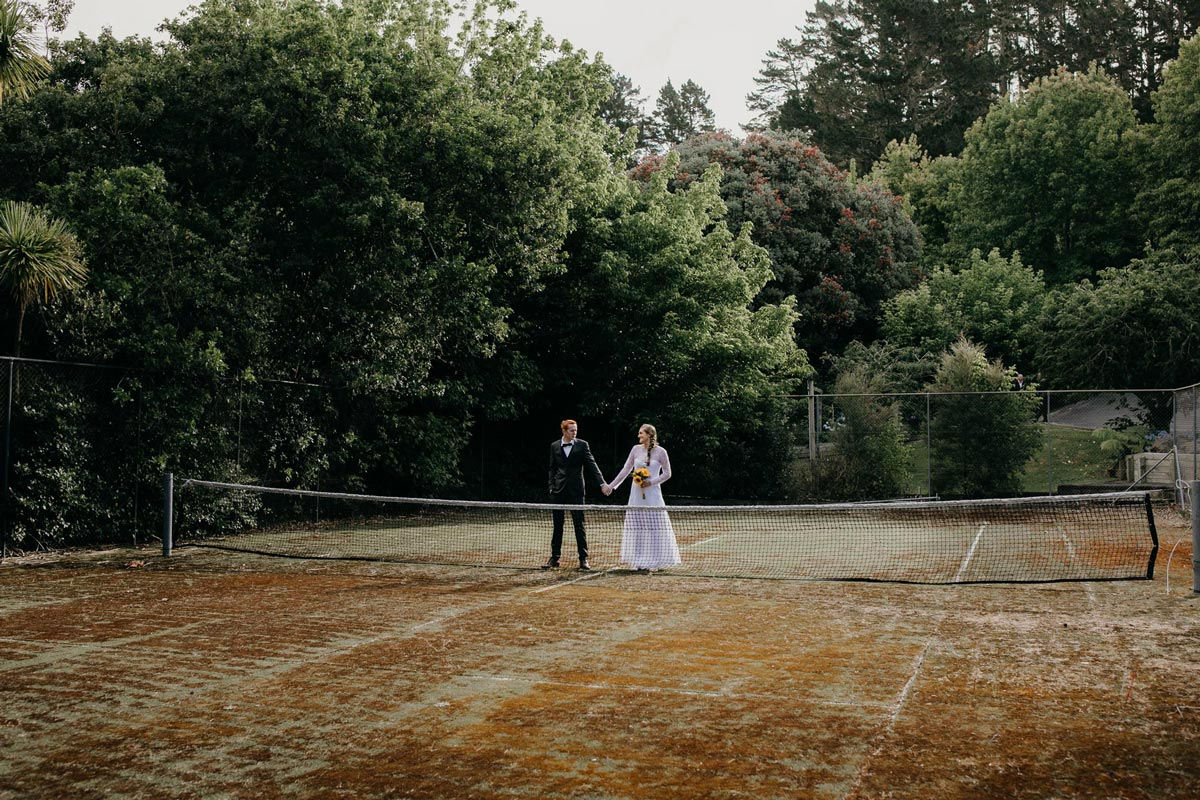 groom and bride creative photos on old tennis court at bridgewater country estate venue in Kaukapakapa, Auckland photo by sarah weber photography