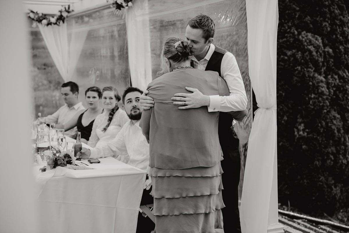 groom kissing his mothers cheek during wedding reception at bridgewater country estate venue in Kaukapakapa, Auckland photo by sarah weber photography