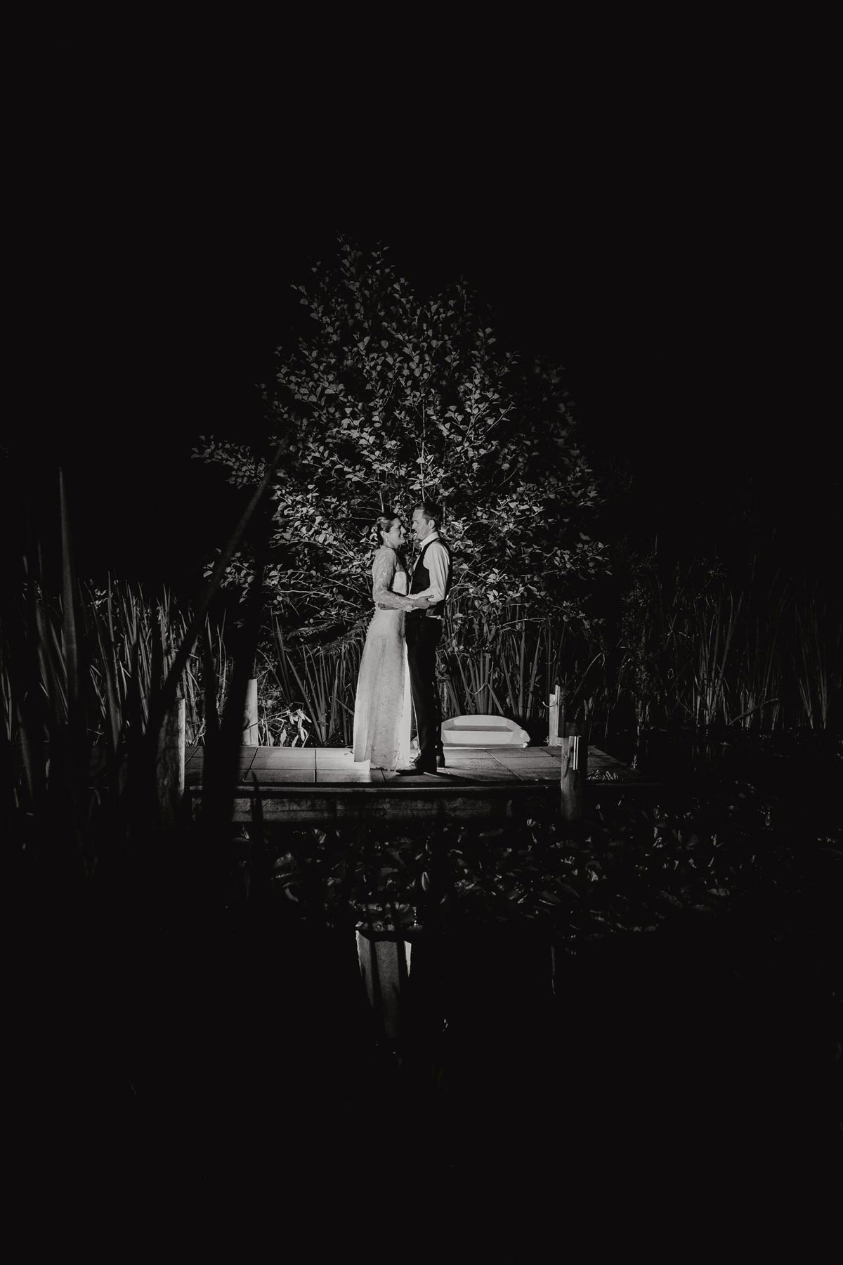 Night backlit creative photos of bride and groom in bridgewater country estate gardens after wedding reception. Venue in Kaukapakapa, Auckland photo by sarah weber photography